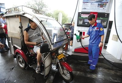 昨日,全市加油站反恐安全大检查专项行动中,某加油站工作人员为持有牌照的三轮车加油。新京报记者 高玮 摄