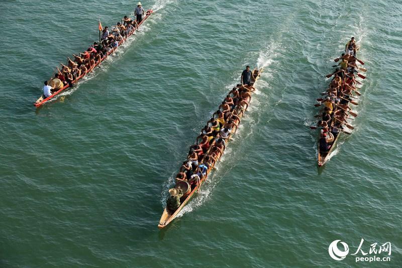 9月6日,在广西柳州市融安县城融江江面上,参赛龙舟队你追我赶,奋勇争先。
